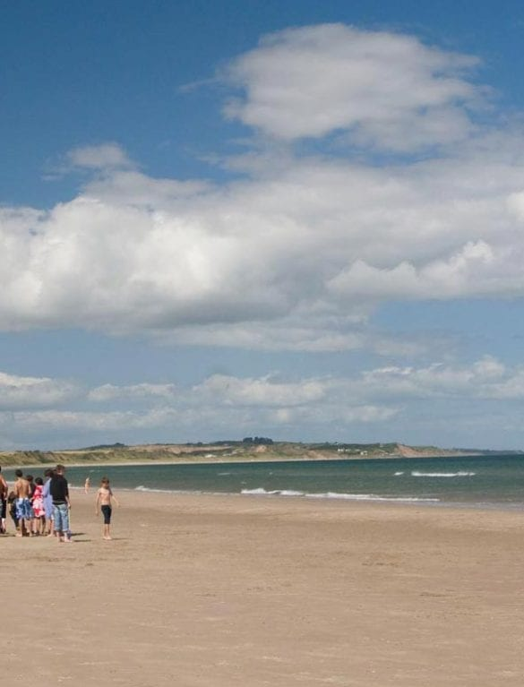 People walking along Curracloe Beach in Wexford